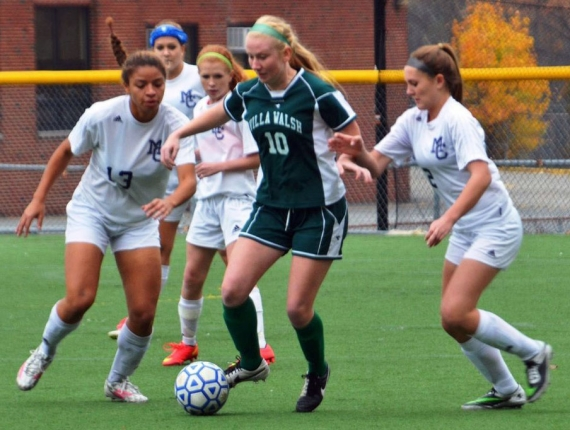 A Villa Walsh player is under pressure from several Morris Catholic players, including Rachel Mills, far left.