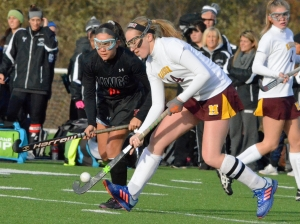 Madison's No. 14, Caroline Blount, has the ball on her stick as Haddonfield's Julia Battino closes in.