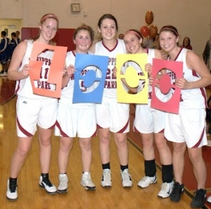Lauren O'Connor, center, poses with several of her teammates after scoring her 1,000th point on Feb. 27.