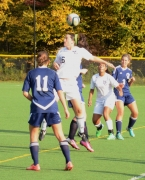 A Morris Catholic player leaps to get her head on the ball.