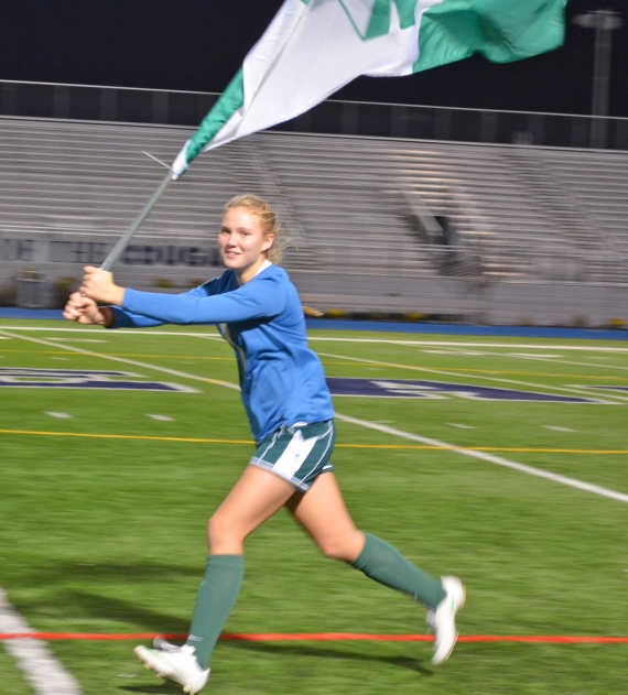 Emma Shatel, who filled in at goalie, runs with the team flag.