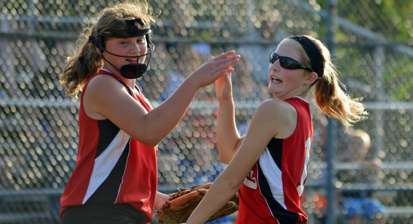 Pitcher Julia Swan and third baseman Megan Gilbert high five after an inning.