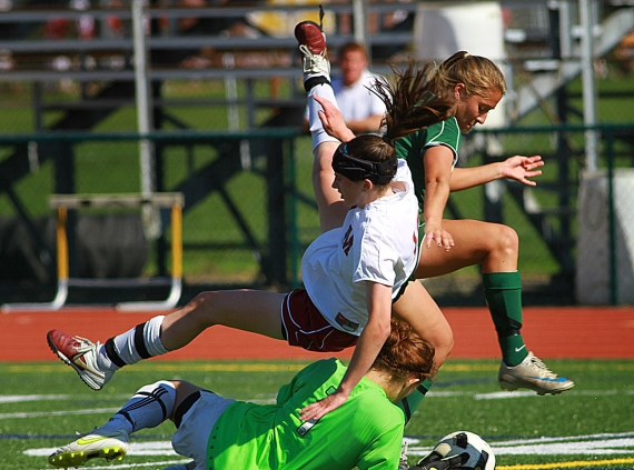 Madison goalie Meg Calcaterra gets tangled up with teammate Rebecca Levin and Morris Knolls' Camille Rosellini.