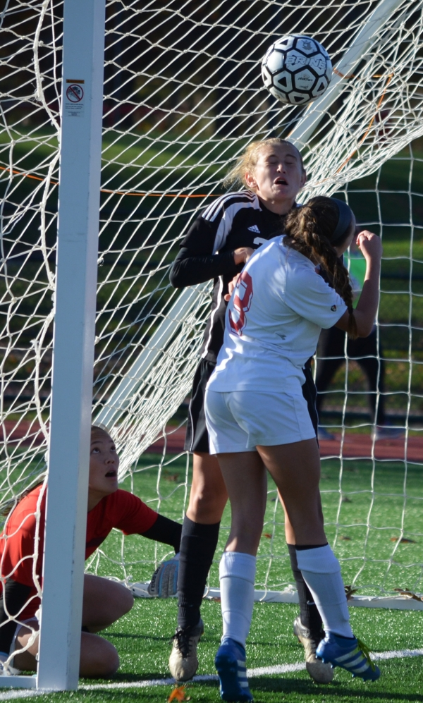 Parsippany's Paige Kaiser, in the forefront, collides with Parsippany Hills' Rebecca Warner, who is attempting to head the ball. Red Hawks goalie Kiera Lewis, left,