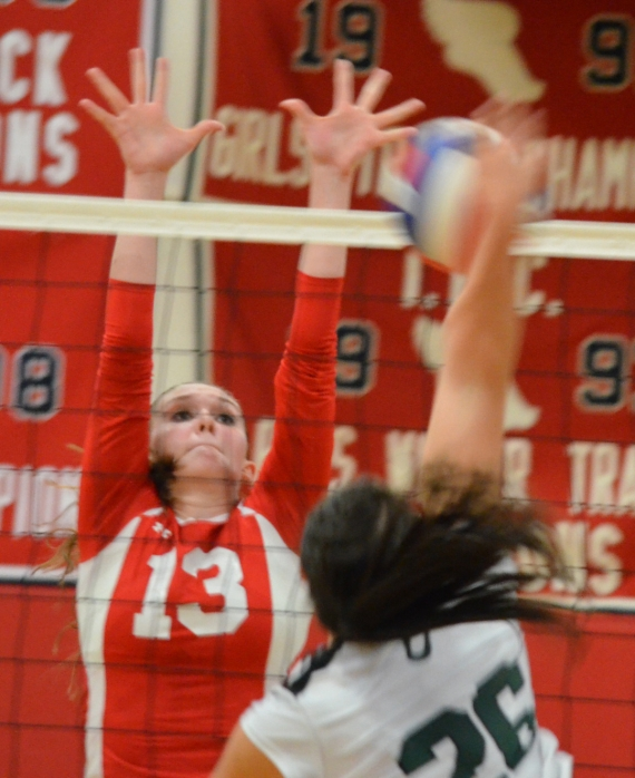 Michaela Sharp of Mendham, in red, goes up to block a hit by Kinnelon's Anthe Stylianou.